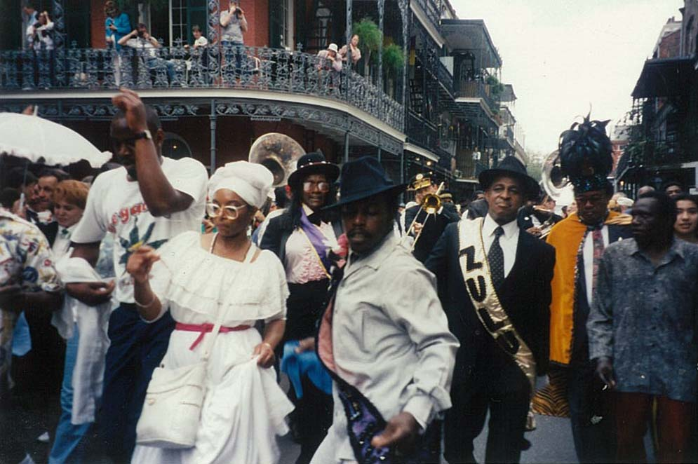 Members of the Krewe of Zulu marching and second-lining down French Quarter