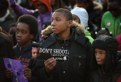 "Anton Watson (center, holding a sign imploring, ""Don't Shoot! I Want to Grow Up"") and other children and youths participate in a peace vigil in the Washington Park neighborhood on November 30, 2012 in Chicago, Illinois. About 75 children, teachers, and parents were joined by area residents and religious leaders as they marched in the streets to draw attention to the violence that plagues their Southside neighborhood. Through the end of October 436 people were murdered in Chicago, surpassing the 435 murders for all of 2011.  (Courtesy:  Scott Olson)"