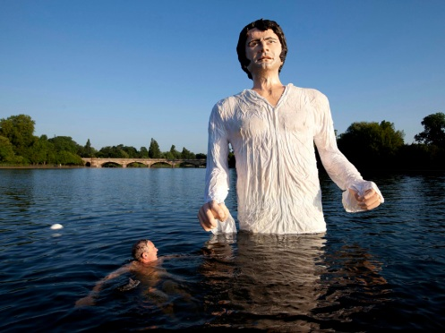 "A swimmer approaches a statue meant to depict actor Colin Firth performing as Mr. Darcy, a character in Jane Austen's novel ""Pride and Prejudice"" at the Serpentine Lake, Hyde Park, London, Monday, July 8, 2013. (Courtesy: AP)"