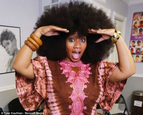 Aevin Dugas peeking out from her enormous Afro at a nearby hair salon in Reserve, LA (Courtesy: Daily Mail)